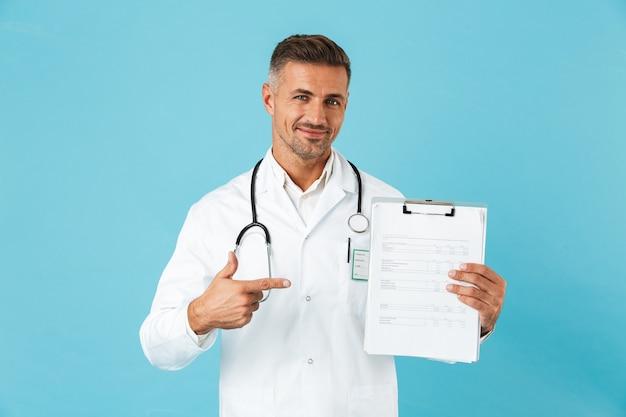 Retrato de um médico alegre com um estetoscópio segurando um cartão de saúde, isolado na parede azul