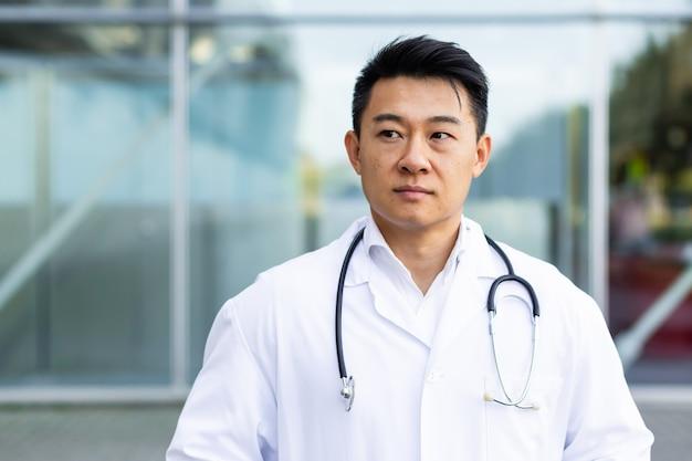 Retrato de um médico asiático sério e severo no fundo de uma clínica moderna ao ar livre