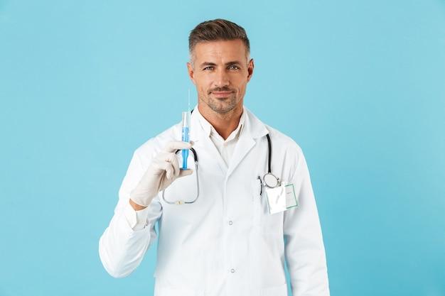 Retrato de um médico bonito com estetoscópio em luvas segurando uma seringa, isolado na parede azul