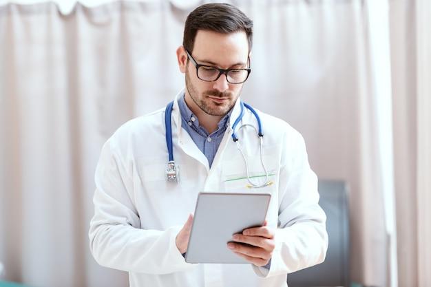 Retrato de um médico caucasiano de uniforme e estetoscópio em volta do pescoço usando o tablet. novas tecnologias em medicina.