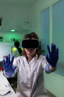 Retrato de um médico cientista químico analisando a experiência de plantas gmo virtuais usando fones de ouvido vr, trabalhando no experimento de microbiologia no laboratório de um hospital de bioquímica. planta com mutação genética