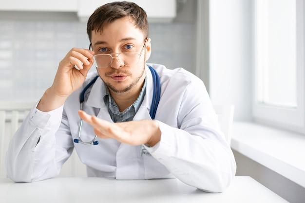 Retrato de um médico com um estetoscópio durante uma consulta por videochamada online.