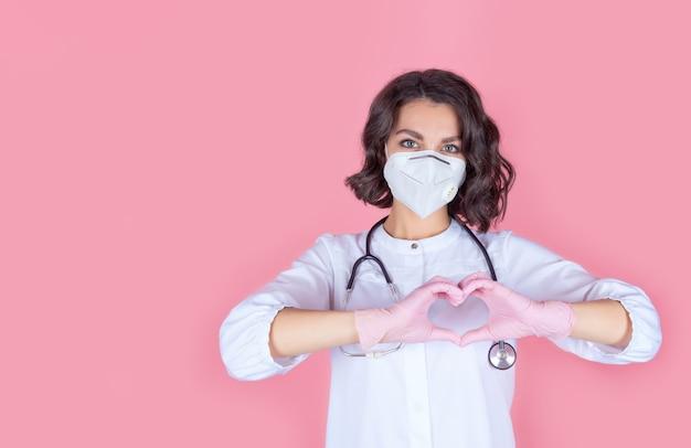 Retrato de um médico com uma máscara de proteção médica com um estetoscópio e luvas de nitrilo rosa mãos mostrando cardiologia de um coração saudável