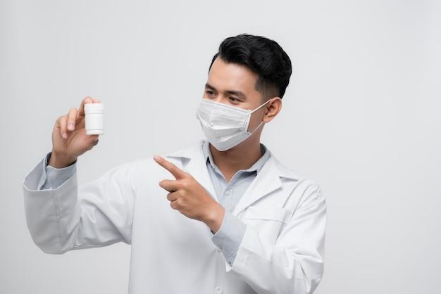 Retrato de um médico confiante vestido de uniforme apontando o dedo para o frasco com comprimidos isolados sobre fundo branco