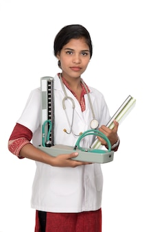 Retrato de um médico da mulher com instrumento de pressão arterial e estetoscópio no espaço em branco.