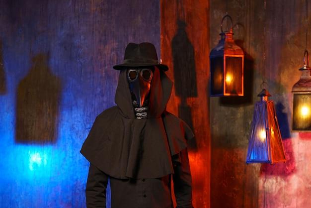 Retrato de um médico da peste com uma máscara de couro preta e um capuz isolado contra uma parede escura