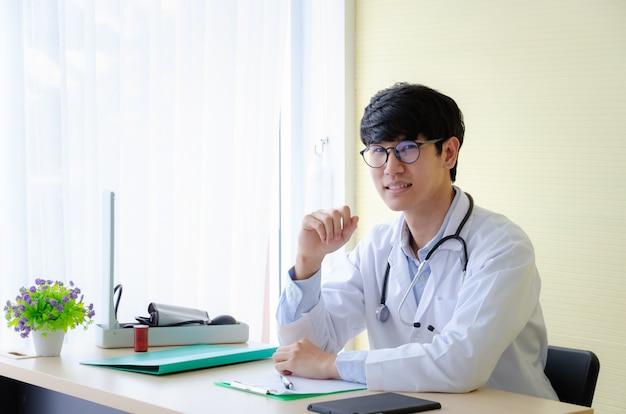 Retrato de um médico em óculos, sentado na mesa. jovem médico sorridente esperando por um paciente