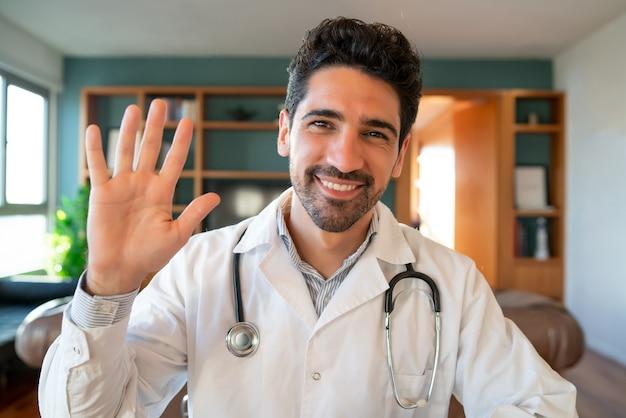 Retrato de um médico em uma videochamada para uma consulta virtual com um paciente. novo estilo de vida normal. conceito de cuidados de saúde e medicina.