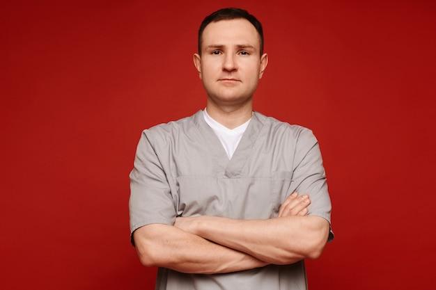 Retrato de um médico em uniforme médico com os braços cruzados, olhando para a câmera nas costas vermelhas.