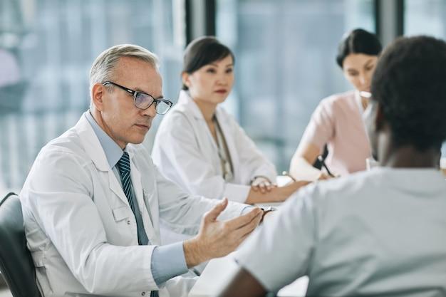 Retrato de um médico especialista conversando com colegas enquanto está sentado à mesa de reunião na sala de conferências durante o seminário médico