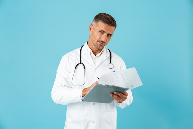 Retrato de um médico europeu com um estetoscópio segurando um cartão de saúde, isolado na parede azul