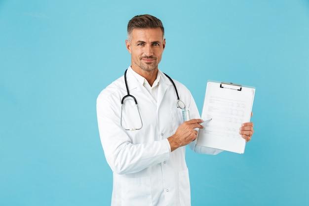 Retrato de um médico gentil com um estetoscópio segurando um cartão de saúde, isolado na parede azul