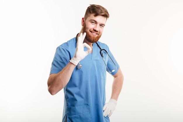 Retrato de um médico homem feliz e amigável mostrando o gesto ok