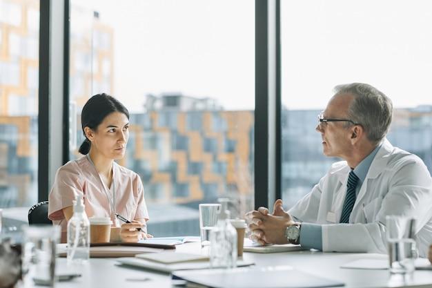 Retrato de um médico maduro falando com um colega enquanto está sentado na mesa de reunião perto da janela