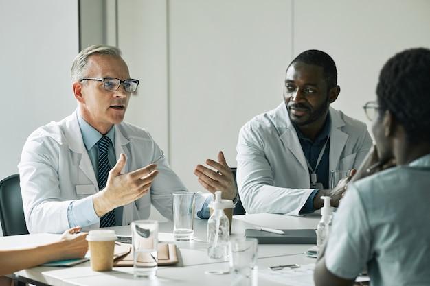 Retrato de um médico maduro sentado à mesa de reunião na sala de conferências enquanto fala com as pessoas durante o seminário médico