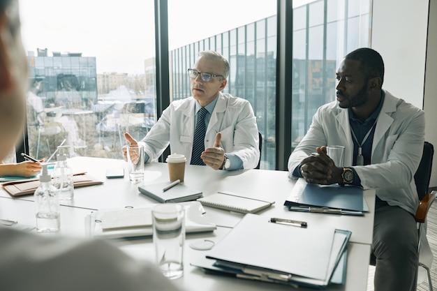 Retrato de um médico maduro sentado à mesa de reunião na sala de conferências enquanto fala durante o seminário médico, copie o espaço