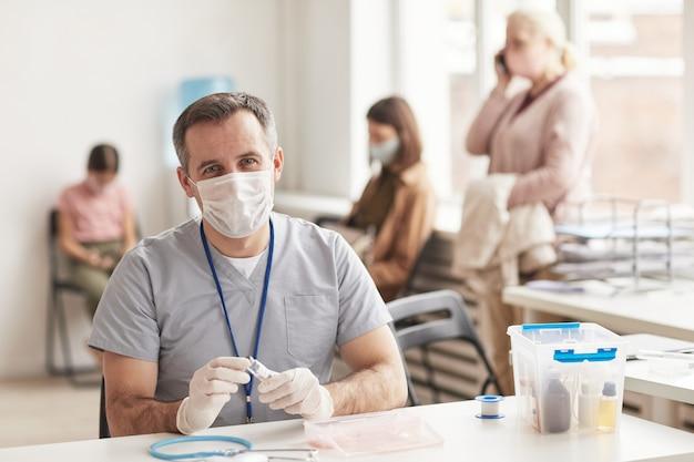 Retrato de um médico maduro usando máscara e olhando para a câmera enquanto está sentado na mesa e esperando os pacientes no centro de vacinação, copie o espaço