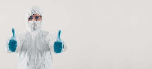 Retrato de um médico na luz de fundo em pé e mostrando os polegares na máscara, luvas médicas e espaço de traje de proteção para texto