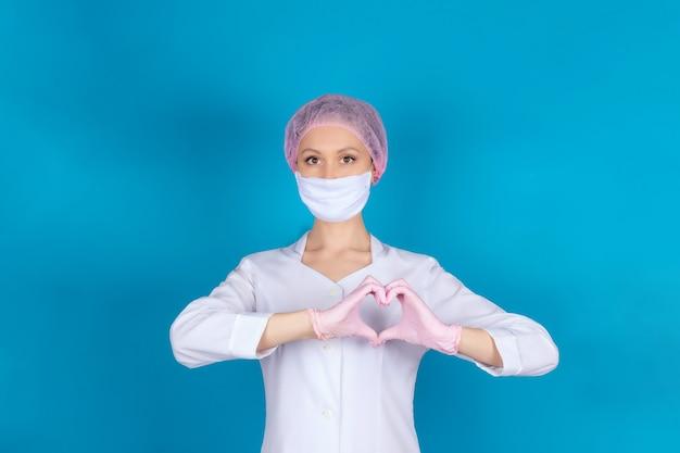 Retrato de um médico ou enfermeiro em uma máscara médica e luvas de nitrilo rosa, mãos mostrando um coração saudável, isolado em uma parede azul.