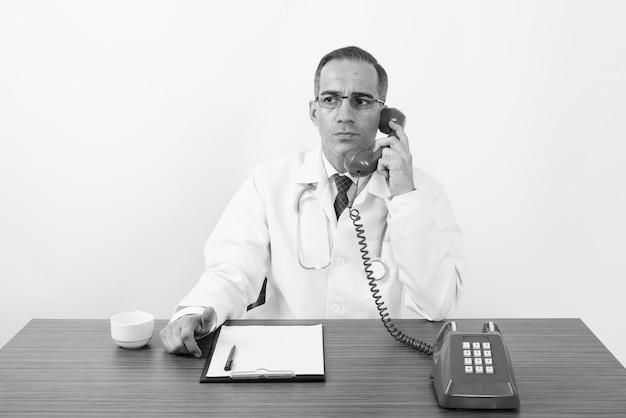 Retrato de um médico persa maduro sentado atrás de uma mesa de madeira em branco em preto e branco