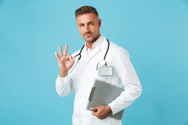 Retrato de um médico profissional com um estetoscópio segurando um cartão de saúde, isolado sobre a parede azul