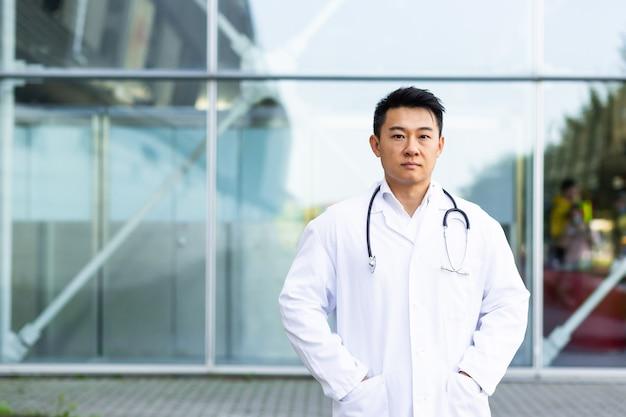 Retrato de um médico sério asiático com os braços cruzados no fundo da clínica moderna ao ar livre