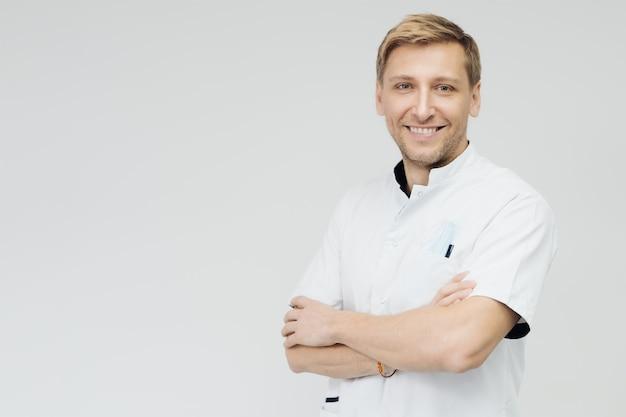 Retrato de um médico sorridente e cruzado as mãos em frente a uma parede branca