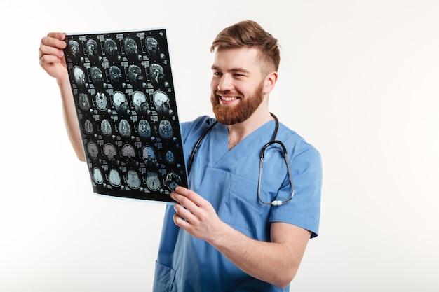 Retrato de um médico sorridente, olhando para a tomografia computadorizada