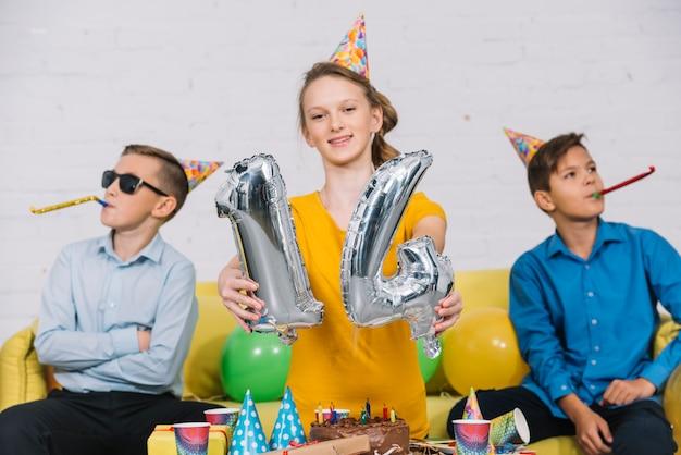 Retrato, de, um, menina aniversário, mostrando, numeral, 14, folha, balloon, com, dela, dois amigos, soprando, partido, chifre