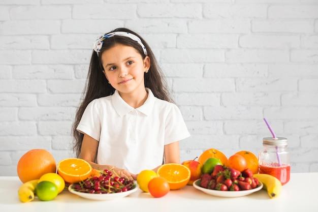 Retrato, de, um, menina, com, muitos, frutas, branco, escrivaninha, contra, parede