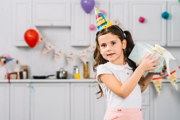 Retrato, de, um, menina, com, presente aniversário, olhando câmera