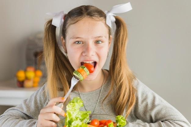 Retrato, de, um, menina, comer, salada vegetal fresca, com, garfo