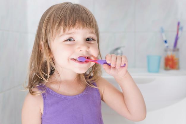 Retrato, de, um, menina, dentes escovando, com, escova de dentes