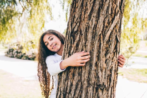 Retrato, de, um, menina feliz, abraçando, grande, tronco, jardim
