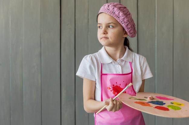 Retrato, de, um, menina, ficar, contra, madeira, cinzento, parede, segurando, escova pintura, e, paleta