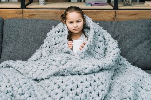 Retrato, de, um, menina, segurando, assalte café, sentar sofá, com, coberto, echarpe