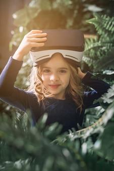 Retrato, de, um, menina sorridente, ficar, entre, plantas, com, virtual, realidade, óculos, ligado, dela, cabeça