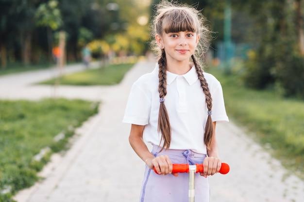 Retrato, de, um, menina sorridente, ligado, empurre scooter, parque