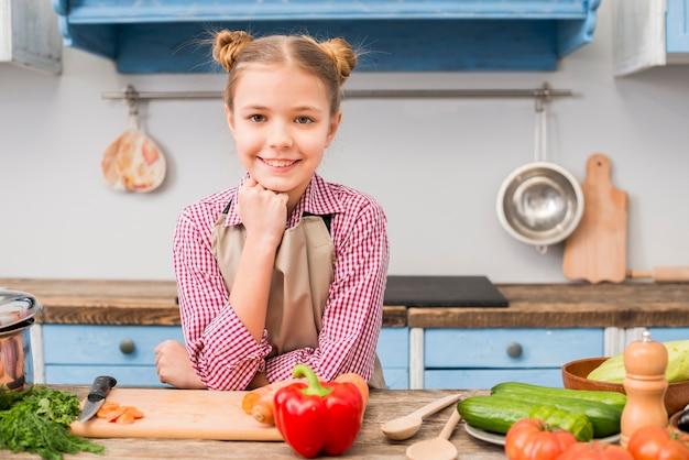 Retrato, de, um, menina sorridente, olhando câmera, ficar, atrás de, a, tabela, com, legumes