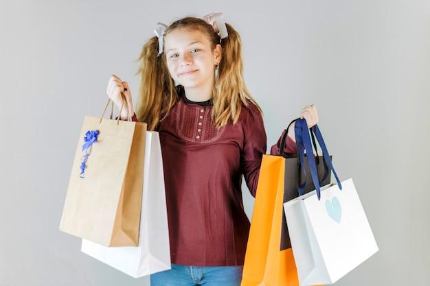 Retrato, de, um, menina sorridente, segurando, bolsas para compras