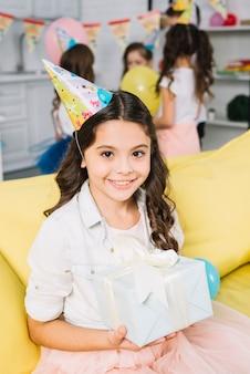 Retrato, de, um, menina sorridente, segurando, presente aniversário, em, dela, mão, sentar sofá