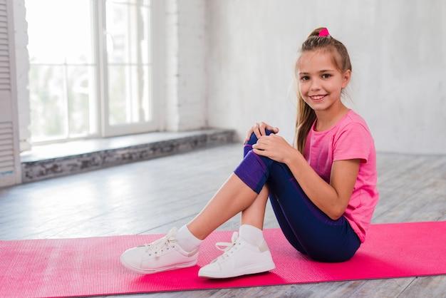 Retrato, de, um, menina sorridente, sentando, ligado, esteira exercício, com, dela, cruzado, pernas