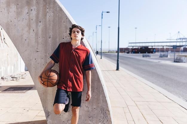 Retrato, de, um, menino adolescente, inclinar-se, parede, com, basquetebol