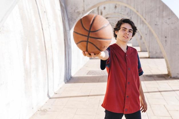 Retrato, de, um, menino adolescente, mostrando, basquetebol