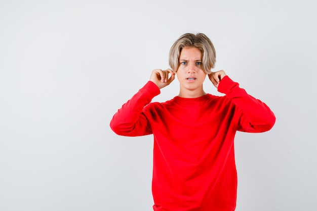Retrato de um menino adolescente puxando para baixo os lóbulos das orelhas com um suéter vermelho e olhando com uma vista frontal curiosa
