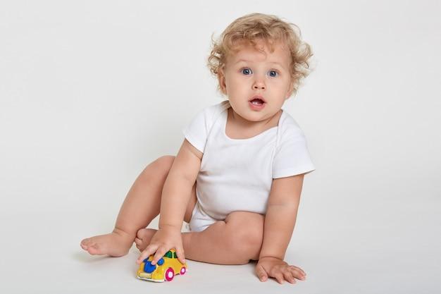 Retrato de um menino adorável sentado no chão, descalço e vestindo macacão