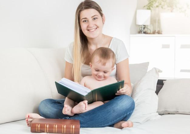 Retrato de um menino adorável sentado no colo da mãe olhando para um grande livro