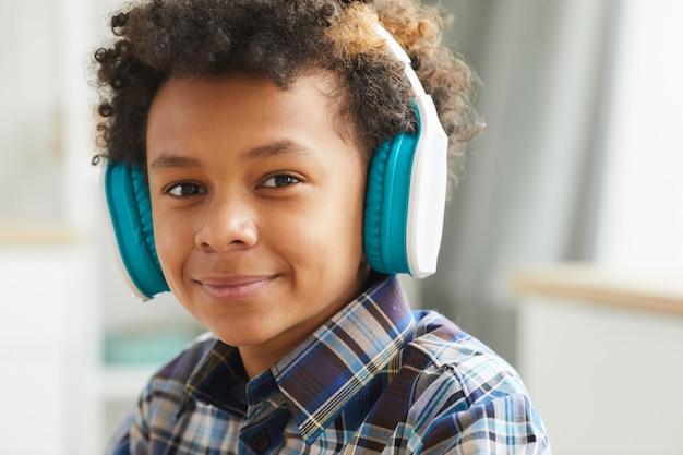 Retrato de um menino africano em fones de ouvido sorrindo enquanto está sentado em casa