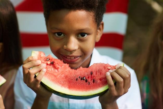 Retrato de um menino africano sorridente segurando uma melancia com a bandeira americana