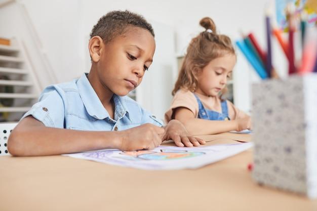 Retrato de um menino afro-americano bonito para colorir imagens com giz de cera enquanto desfruta de aulas de arte e artesanato na pré-escola ou no centro de desenvolvimento infantil